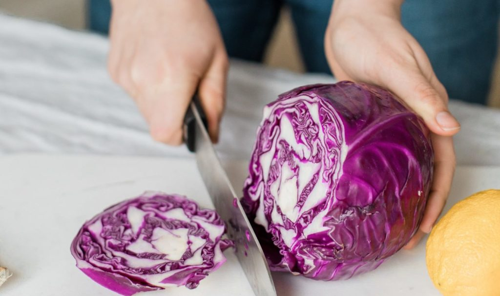 woman slicing purple vegetable